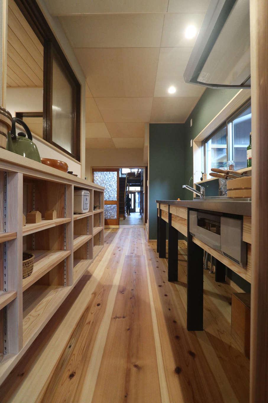 アクトホーム(木の住まいづくり研究所)|動線に配慮し、DKはレイアウトを変更。引き出しを備えたオリジナルの造作キッチンと高さ可変の収納が家事効率を高めるとともに、ムク材とアクセントのモスグリーンがもたらすナチュラルな雰囲気にマッチしている。右手にはタイル仕立ての洗面台を用意