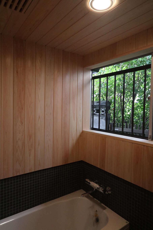 アクトホーム(木の住まいづくり研究所)|ヒノキとモザイクタイルで仕上げられた浴室には、清々しい香りと落ち着きが満たされ、ゆったりとバスタイムを過ごすことができる。脱衣室との仕切りとなる引き戸には水に強く耐久性の高いヒバを使用するなど、適材適所で樹種や部位が選ばれている