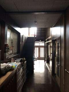 リノベ後、通り土間に生まれ変わった廊下を玄関から見通す。天井にも新建材が張られた空間は、昼でも明るさが十分とはいえず、通路以上の役割を持ち得なかった