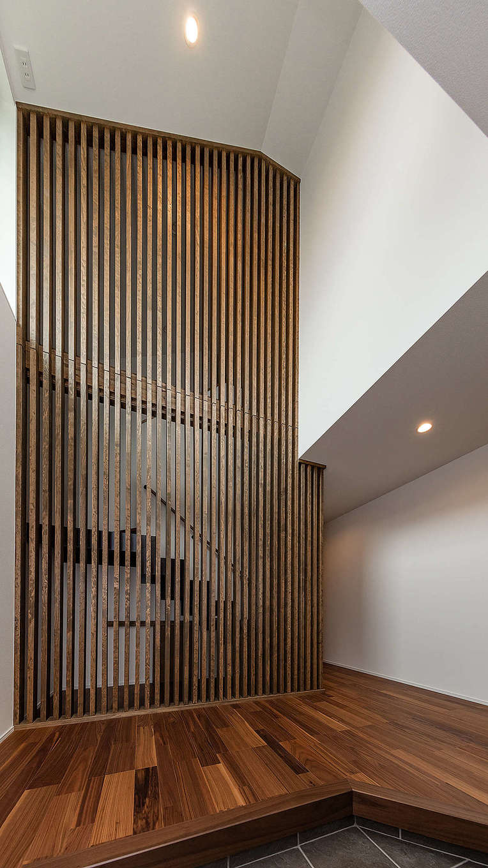 内田建設【収納力、間取り、建築家】清々しさが漂う玄関ホール。天井まで届く格子が格段を緩やかに隠すと同時にインテリアの一部にもなっている