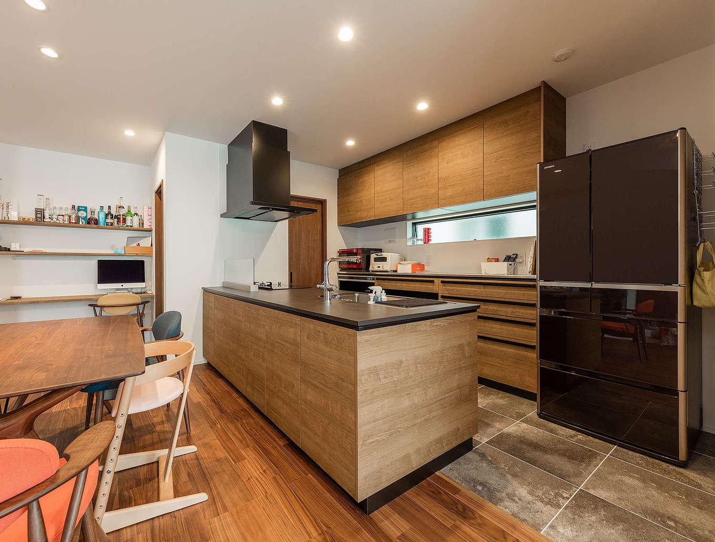 内田建設【収納力、間取り、建築家】フローリングの色と質感に合わせて選んだキッチンはクリナップの「セントロ」。 ガスと電気一体型の最新モデルをセレクトした。2WAYのパントリーも便利。夫婦が好きなお酒のボトルを棚に飾って暮らしを楽しむ