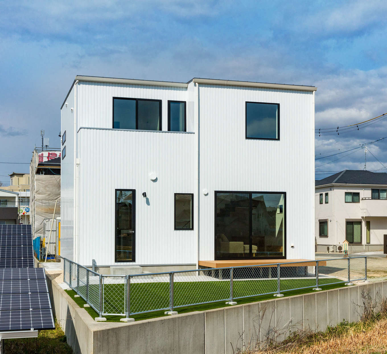 内田建設【デザイン住宅、間取り、建築家】窓を大きくとり、光と風をたっぷりと招き入れる南側の外観。独特な土地形状を活かして、庭も広く確保できた。アメリカンフェンスもおしゃれ