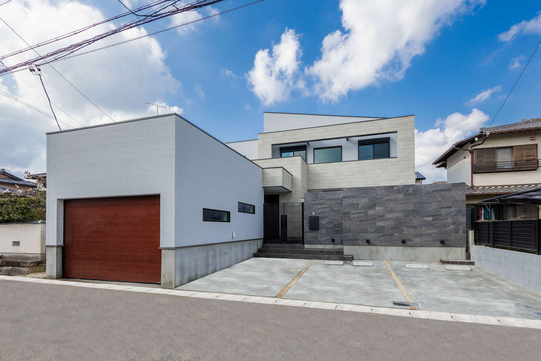 内田建設【デザイン住宅、建築家、ガレージ】建築家ならではの独創的なデザインが美しいガレージ一体型のF邸。外壁のタイルが高級感を演出。中庭と広いテラスがあり、目線を気にせずBBQやプールを楽しめる