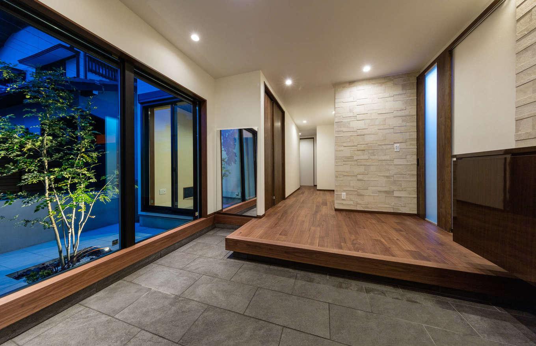 内田建設【デザイン住宅、建築家、ガレージ】ガレージからもアクセスできる通り土間のある玄関ホール。庭の植栽を眺めながらリビングへと向かう
