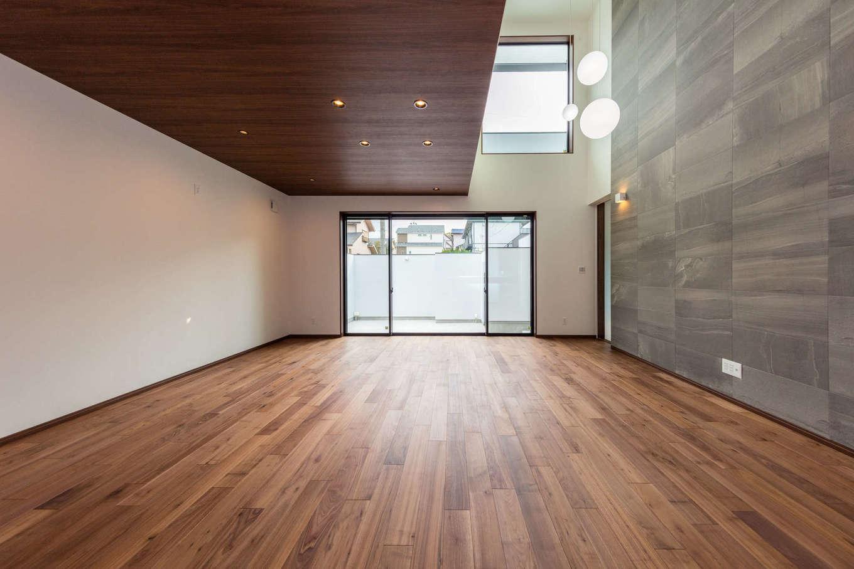 内田建設【デザイン住宅、建築家、ガレージ】リビングダイニングの天井に木を使い、吹抜けのテレビステーションにタイルを貼った大胆なインテリア。2階の大きな開口部から燦々と光が降り注ぐ