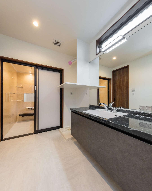 内田建設【デザイン住宅、建築家、ガレージ】ホテルライクなパウダールーム。黒い人造大理石の洗面台、大きな鏡が素敵
