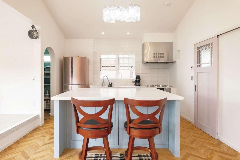 イデキョウホーム【輸入住宅、省エネ、平屋】キッチンは白いタイルで洗練されたデザインに。特注のアイランドキッチンは多彩な収納に複数のコンセントと機能性も抜群。右手の扉の先には水回りをまとめ、家事効率を高めた