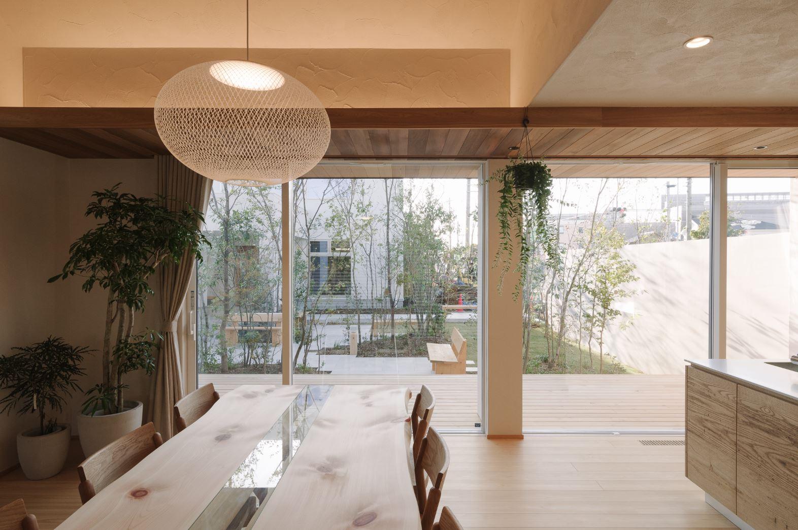アイジースタイルハウス【浜松市東区和田町439-1・モデルハウス】天井まで届くフルハイサッシを採用したことで、外と中のつながりが感じられ、四季折々の庭の景色を眺めながら暮らせる。これだけ大きな窓を使っても、「地球品質」の家だから結露知らず。無垢の床、漆喰の塗り壁の経年変化も楽しみだ。ヒノキ丸太のスライステーブルは同社のオリジナル製作