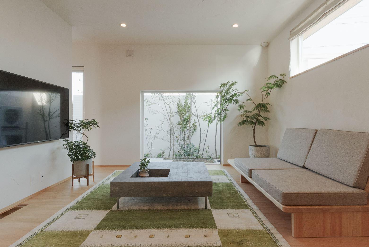 """アイジースタイルハウス【浜松市東区和田町439-1・モデルハウス】ホームシアター感覚でゆったりとくつろげるリビング。大きなFIX窓に映る中庭のビオトープは、額縁で切り取った写真のように見える。まさに""""感情がデザインされる""""空間だ"""
