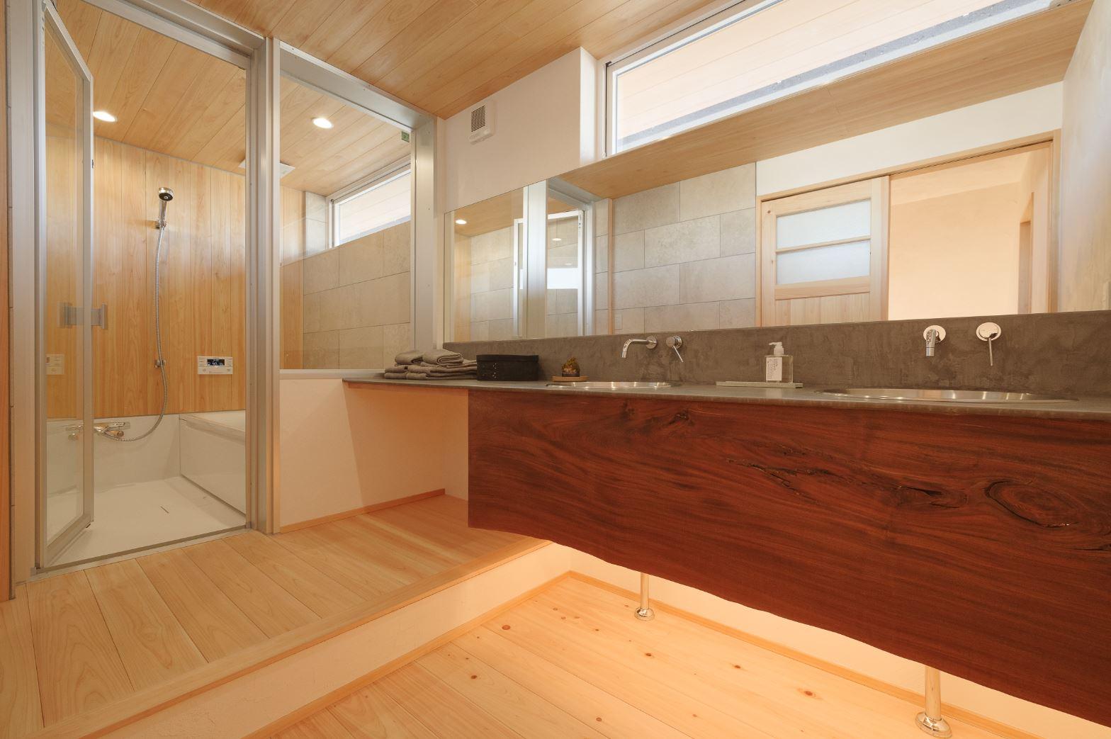 アイジースタイルハウス【浜松市東区和田町439-1・モデルハウス】2階の浴室は、ひのきと石で造作したハーフユニット仕様。宙に浮かぶようにデザインされたパウダーコーナーは、 シンクを2つ設けたことで忙しい朝の混雑も解消できる。透明のガラスとワイドな鏡を採用したことで、より開放感が生まれた