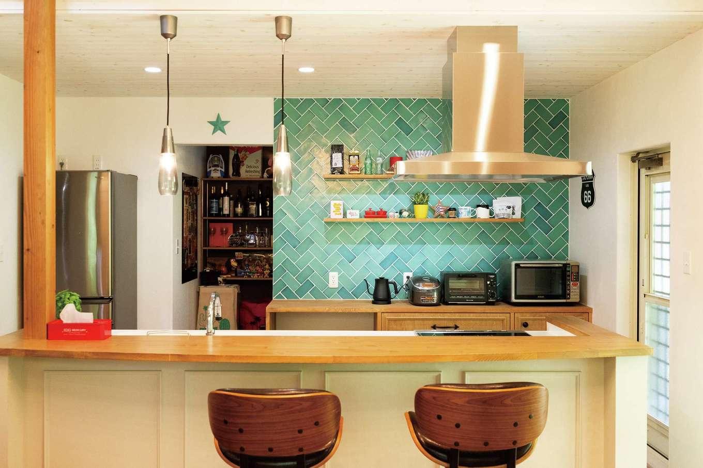 富士ホームズデザイン【デザイン住宅、子育て、インテリア】キッチンは微妙に異なる色合いのタイルがアクセント。カウンターやキッチンボードは空間の雰囲気にあわせてシンプルに。奥は大容量で使い勝手にも配慮したパントリー