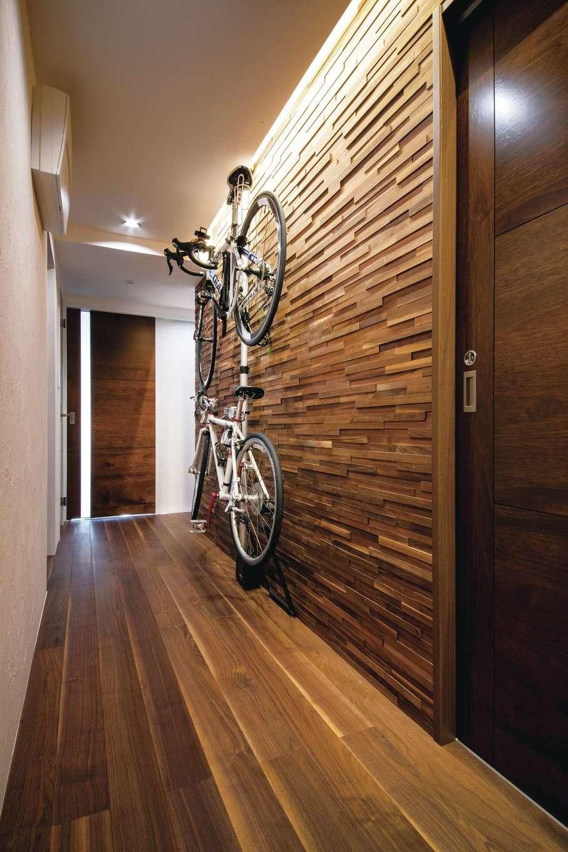 CLASSICA HOME/クラシカホーム|玄関からリビングにつながる長い廊下。幅を20cm広げただけで暮らしやすさが倍増した。以前から自転車を飾っていた壁をクロスからウォルナットのウッドタイルに変え、さらに間接照明をあてて、ギャラリーのような雰囲気に