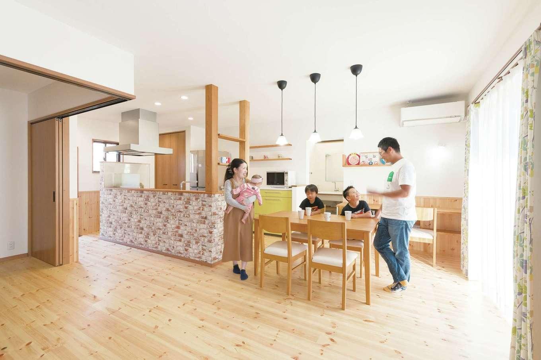 四季彩ひだまり工房 高田工務店【デザイン住宅、子育て、間取り】20畳のLDK。無垢のパイン材の床は、真冬でもスリッパなしで過ごせるほど暖かい肌触りでリラックスできる。経年変化も楽しみ。ダイニングテーブルをキッチンの横にレイアウトしたことで、配膳や片付けをスムーズにこなせる。客間は普段はオープンにして開放的な雰囲気に