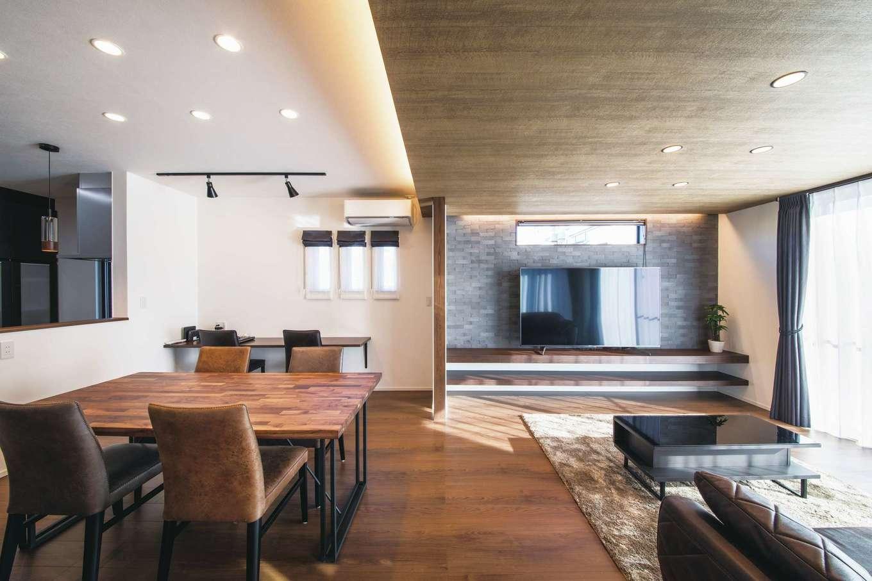 スズイチ【デザイン住宅、平屋、ガレージ】板張りの天井と造作のTVボード、石目調のアクセントクロスがベストマッチなリビング。ダイニングの窓辺にはカウンターを設けてあり、パソコン作業やちょっとした書き物などに利用。ホームパーティの際にはゲスト用の席としても活躍