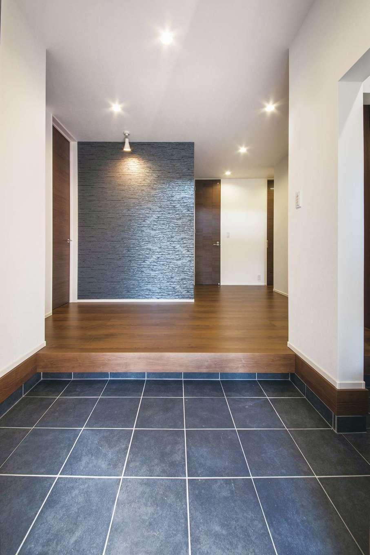 スズイチ【デザイン住宅、平屋、ガレージ】大勢の来客に対応できるように、土間とホールにゆとりを持たせた玄関。正面には石目調のアクセントクロスを用い上質感を演出