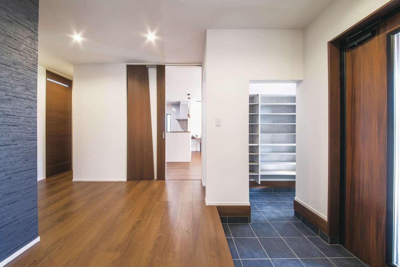スズイチ【デザイン住宅、平屋、ガレージ】玄関はシューズクロークからも上がれるようになっている。室内にはハイドアを採用し、いっそう開放感が強調されている