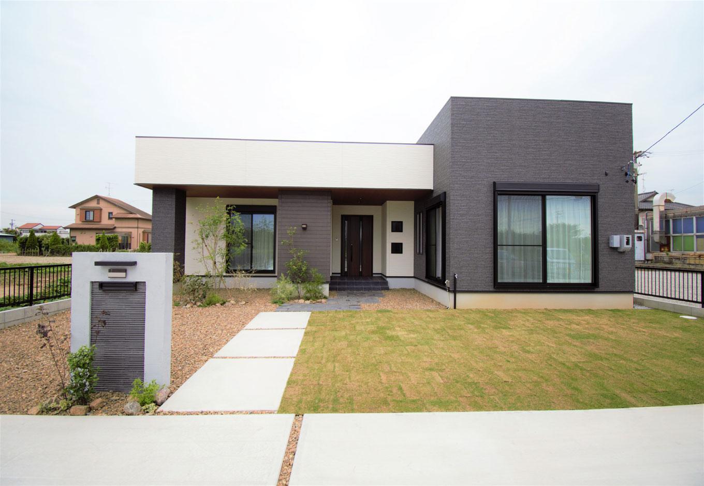 スズイチ【デザイン住宅、平屋、ガレージ】モノトーンで統一した箱型の外観は、道ゆく人が思わず足を止めるほどインパクトのあるデザイン。黒い外壁部分はLDKにあたり、天井を高くしてある
