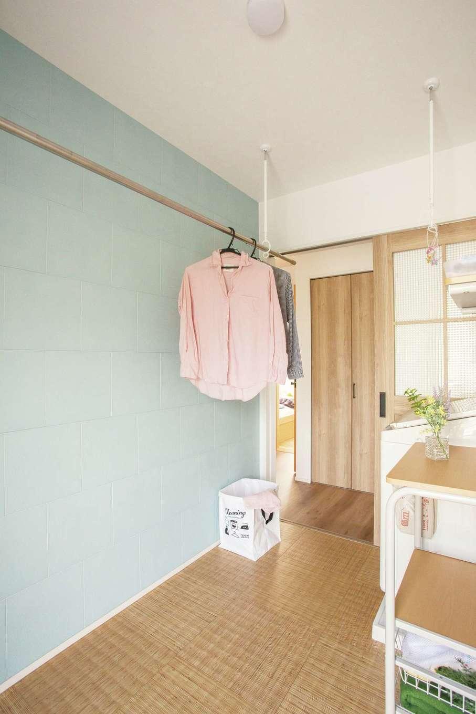 casa carina 浜北(内藤材木店)【デザイン住宅、自然素材、インテリア】洗面・脱衣室の隣に設けたランドリーは、室内干しと収納棚付きで、洗濯の作業が1か所でできる。勝手口もあるので、屋外に洗濯物を干すときにも動線が短くて便利。壁面に貼った水色のエコカラットが湿気を吸い取るため、洗濯物も乾きやすく、室内干しのニオイも付きにくい