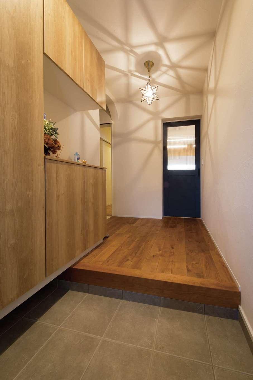 コバケンホーム(小林建設)【子育て】奥さまのこだわりのペンダント照明が漆喰壁に幾何学模様の影を美しく描き出す玄関。玄関収納もたっぷり設けてある