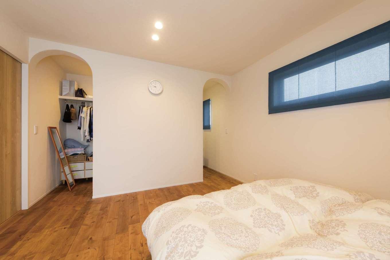 コバケンホーム(小林建設)【子育て】寝室のウォークインクローゼットは、アーチ型の出入り口がロマンチック。ベッド側の窓は周囲の視線に配慮して横長に設けてある