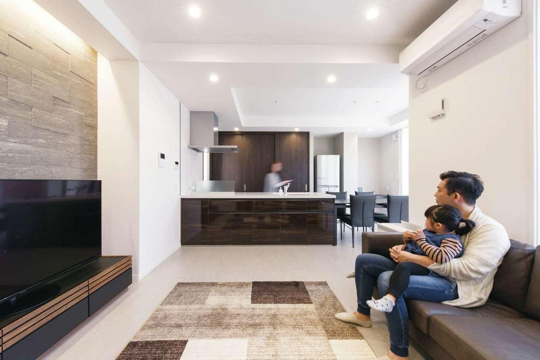 デザインハウス【デザイン住宅、スキップフロア、インテリア】間接照明がラグジュアリー感を醸し出すLDK。大理石調のフロアタイルをベースに白を基調とした空間が実寸以上の広がりを感じさせる。奥さまの要望で、キッチンからテレビが見えるようにリビングを配置。調理をしながらリビングにいる家族との会話も楽しめる