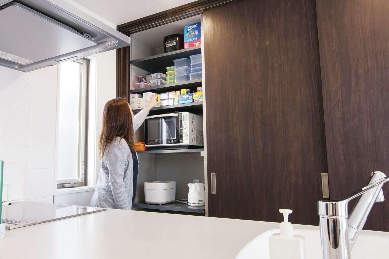 デザインハウス【デザイン住宅、スキップフロア、インテリア】「LDKを常に美しくキープするため、生活感を排除したい」と希望した夫妻。そのため、キッチンの背面に大きな扉の「隠す収納」を確保し、食器や電化製品、キッチン用品、ストック食材などをまとめてしまえるようにした。普段は扉をオープンにしておき、「調理中にパッと後ろを振り返るだけで必要な物を取り出せるのですごく便利です」と奥さま。タッパーのような軽いものは上部の棚に置いてあり、よく使うものは手の届きやすい場所に配置されている