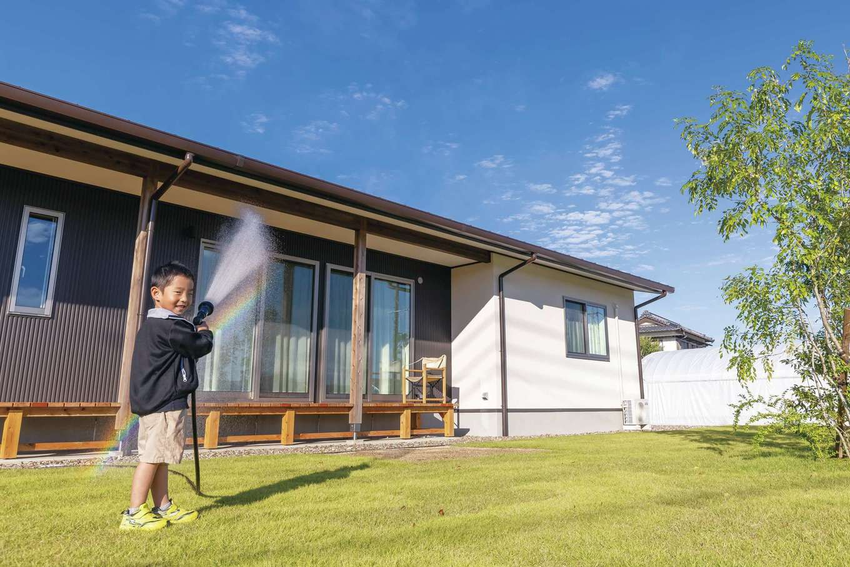新栄住宅【趣味、自然素材、平屋】広い庭は、体力があり余っている子どもたちの絶好の遊び場。時々、奥さまも芝生の上でトランポリンを楽しんでいる
