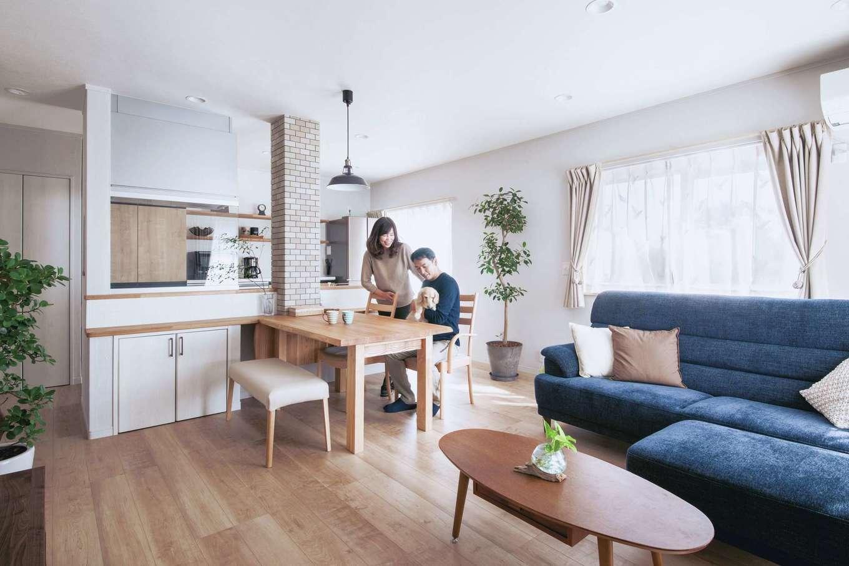 ほっと住まいる|ナチュラルな色の床に、塗り跡さえ美しい塗り壁の白が映える。火砕流の堆積物を生かしたシラス塗り壁は、調湿効果や消臭効果も期待できて、いつも空気を清々しく保ってくれる。キッチンを囲む造作カウンターとダイニングテーブルは、『ほっと住まいる』からのプレゼントで、タモ材の優しい色合いが目に優しい。奥さまが選んだフランスゴムの木など、鉢植えのグリーンが彩りを添えている