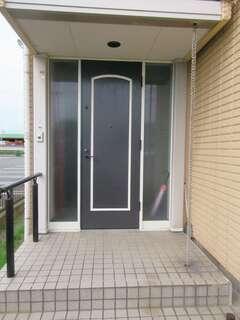 玄関周りの壁を外壁の色に合わせ、ドアをLDKのテイストに通じる木製に変更。これだけで雰囲気が一変した