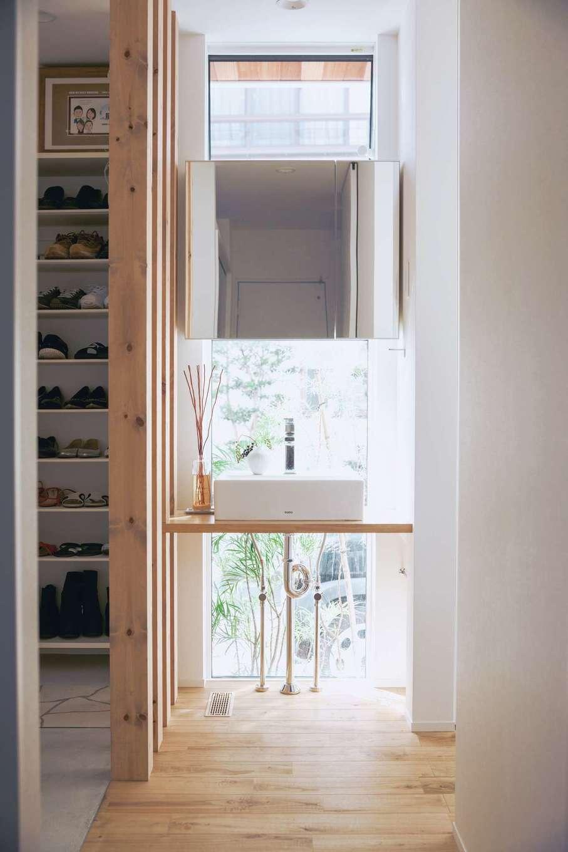 ワンズホーム【デザイン住宅、狭小住宅、建築家】玄関ホールや靴収納のそばにある、造作洗面台はすっきりとしたたたずまい。「建築中に、やっぱり壁をやめて格子にしていただけるようお願いして大正解でした」と奥さま。空間全体が明るい
