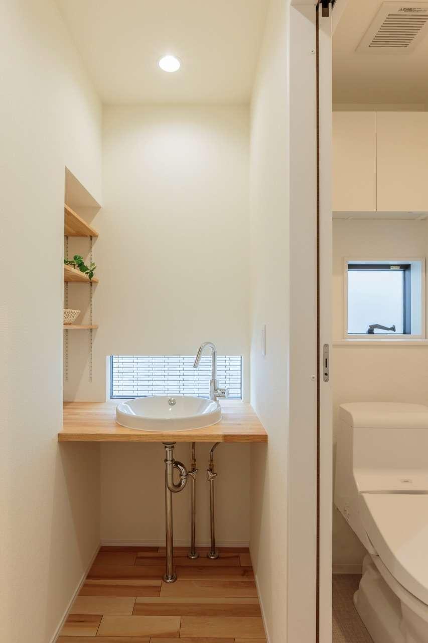 寿鉱業 ナーブの家【デザイン住宅、省エネ、間取り】2階のトイレの横に設けた手洗いカウンター。壁面を収納棚に利用し、シンプル&コンパクトでありながら機能的