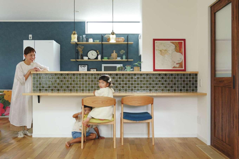 アイフルホーム 掛川店【デザイン住宅、子育て、間取り】カウンター付きキッチンには、奥さまが吟味したタイル壁を採用。キッチン背面にはアイアンの飾り棚があり、奥さまがディスプレイした雑貨が並ぶ。家事時間が楽しくなりそう
