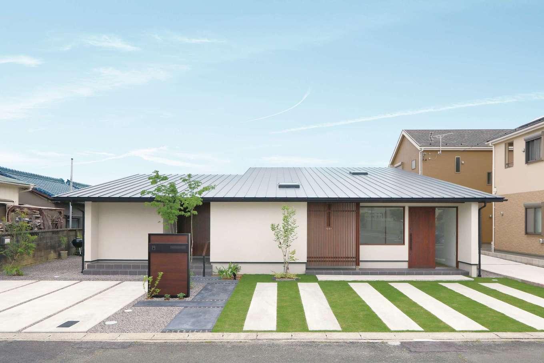 神谷綜合建設 カミヤの家【デザイン住宅、収納力、平屋】片流れの大屋根を抱く、堂々たる佇まいの外観。軒の高さをできるだけ低くし、塗り壁に杉の格子が映える洗練されたデザイン。ギャラリーの入口が分かるよう、住居の玄関はあえて引き込ませ、目立たないように配慮