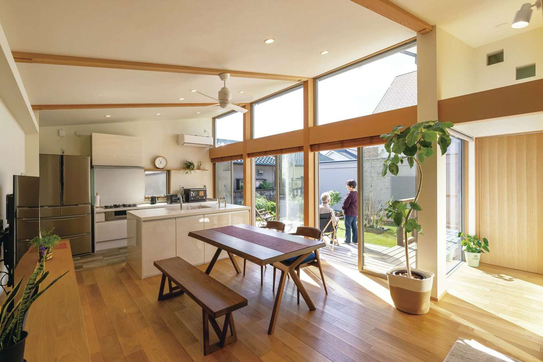 神谷綜合建設 カミヤの家【デザイン住宅、収納力、平屋】玄関ホールを抜けると、大開口の窓を持つLDKがお出迎え。落ち着きのあるヨーロピアンオークの床をベースに、木目の詰まった見た目にも美しいピーラー(米松)の化粧柱や、壁面にレッドシダーを採用することで、程よい木質感を演出。壁の一部にあしらった、通気性や透湿性に優れたコットンクロスが窓からの光を優しく反射し、室内を照らす。L字のプランにしたことで部屋のどこからでも庭を望むことができ、明るく、居心地のよい空間になった