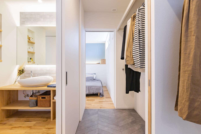 ARRCH アーチ【浜松市東区西ケ崎町1331・モデルハウス】寝室と水回りを結ぶウォークスルークローゼット。洗面スペースは浴室と独立させ、ランドリーと仕切ることもできるので、来客時に生活感をすっぽりと隠すことができる。手前のランドリーに干した衣類が乾いたら、そのままクローゼットにハンガーを掛け替えるだけで済むので、家事も楽々