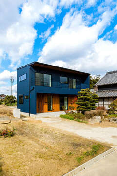 濃紺のガルバと木の色が鮮やかな外観の北欧モダンの家
