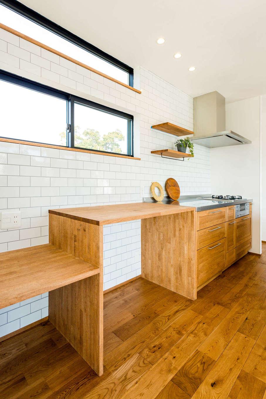 アトリエプラス【デザイン住宅、趣味、自然素材】パン作りが趣味の施主さんのため、キッチンはアイランド型と壁付け型の両方で、広い作業スペースを確保。壁面の主張し過ぎないタイルはどんなインテリアとも調和する