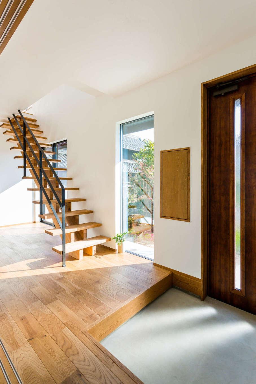 アトリエプラス【デザイン住宅、趣味、自然素材】大きな窓からのたっぷりの採光で明るい玄関まわり。木とアイアンで無骨に仕上げたオープン階段が目を引く