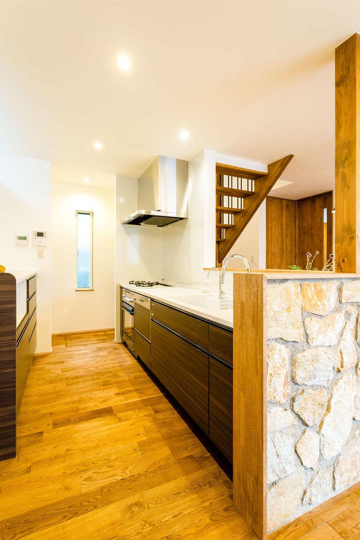アトリエプラス【デザイン住宅、自然素材、インテリア】家族とコミュニケーションがとりやすいペニンシュラ型を採用。キッチンのダークブラウンと石壁がリビングにマッチし、インテリア性と機能性を両立
