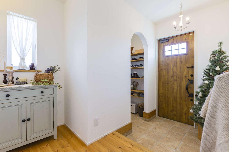 cozy house(小塚建設)【デザイン住宅、ガレージ、インテリア】ゆったりとした玄関ホール。当初収納を造作する予定だった部分はフリースペースにして、リビングの建具と同じシャビーシックな色合いのチェストを設置