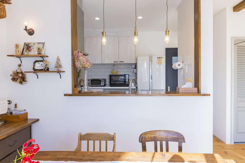 cozy house(小塚建設)【デザイン住宅、ガレージ、インテリア】カフェのようなキッチン。背面には艶やかさが魅力のタイルを貼った。ダイニングの一角には、家族で多目的に使えるカウンターテーブルを造作。シェルフと照明の位置も絶妙なバランス