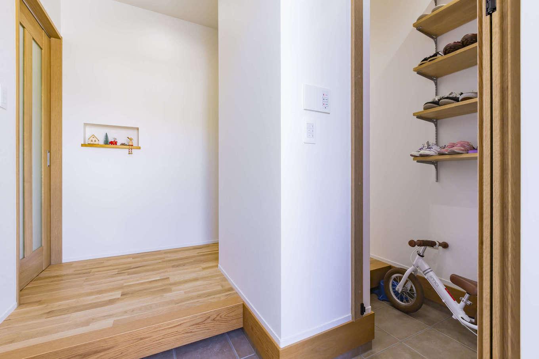 cozy house(小塚建設)【デザイン住宅、収納力、間取り】来客と家族の動線を分けた玄関。仕切り壁のシューズクローク側には上着を掛けるハンガーポールを設置