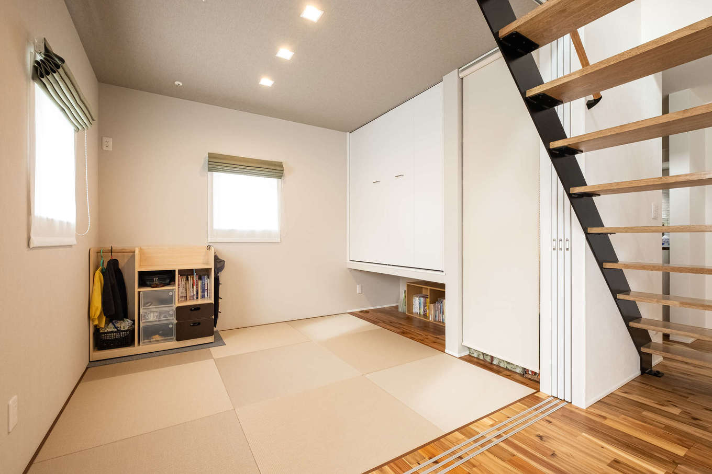 R+house御殿場(岳南建設)【収納力、間取り、建築家】リビングから続く和室。吊り収納の下は子どもの本棚に活用。ゲストが泊まるときには荷物を置くこともでき、部屋を広く使える。ロールスクリーンで目隠し可能なオープン収納はおもちゃ置き場に