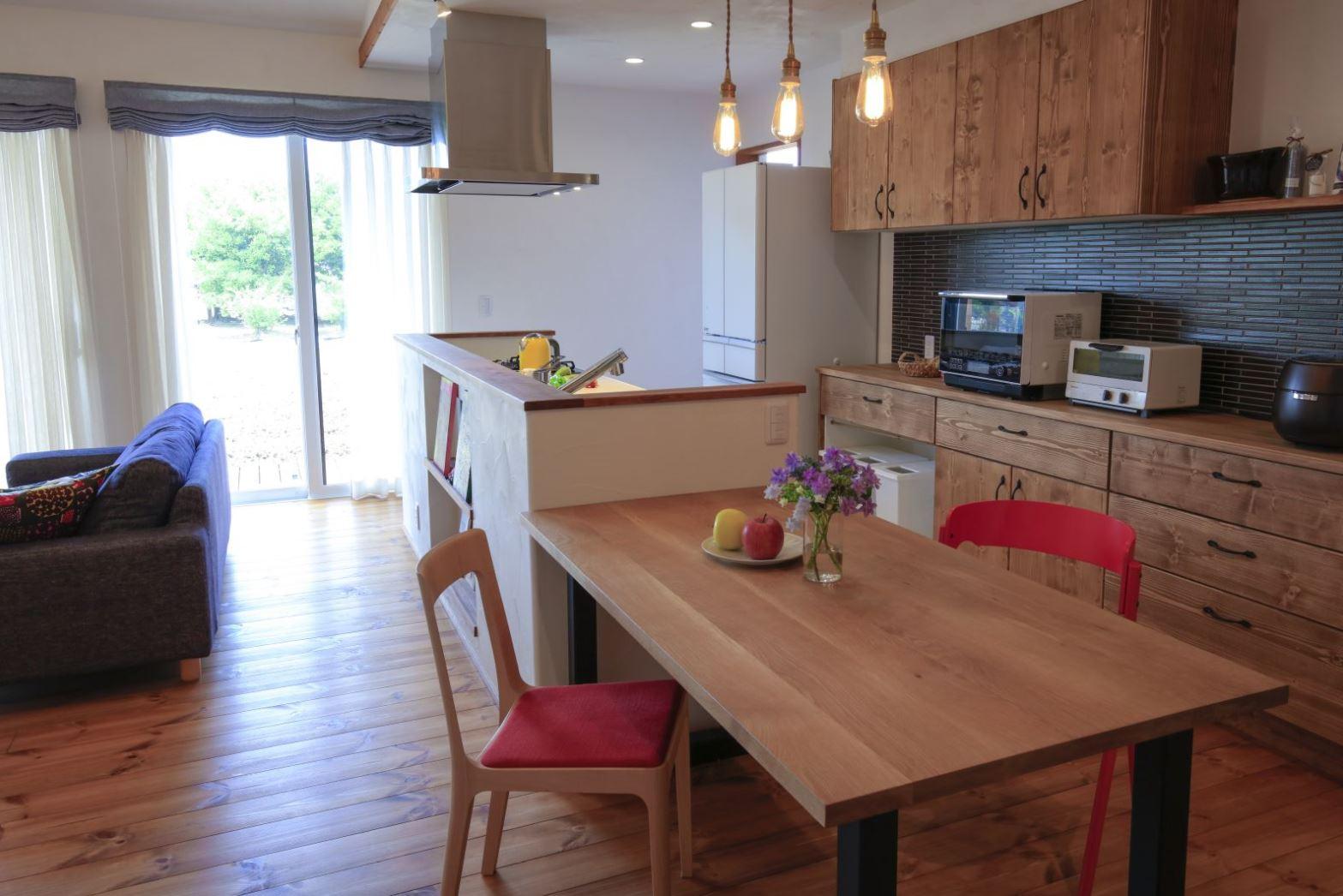 アイジースタイルハウス【自然素材、間取り、平屋】キッチンとダイニングテーブルを横一列にレイアウトしたことで家事効率も大幅にUP。ご主人も使いやすいよう、カップボードはすべて引き出しタイプに。シックなボーダータイルもお気に入り