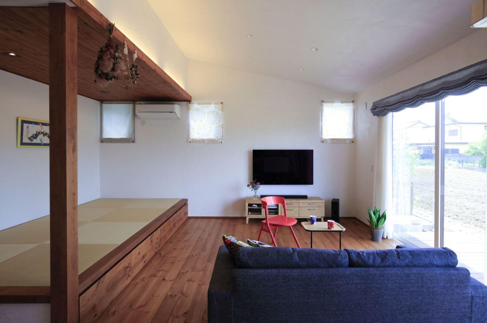 アイジースタイルハウス【自然素材、間取り、平屋】勾配天井を採用し、より開放的に感じられるリビング。小上がりの畳コーナーは、ちょっと横になったり、腰掛けたり、洗濯物をたたんだりと大活躍。羽目板の天井が落ち着いた雰囲気をもたらす。畳の下は大容量の収納スペース