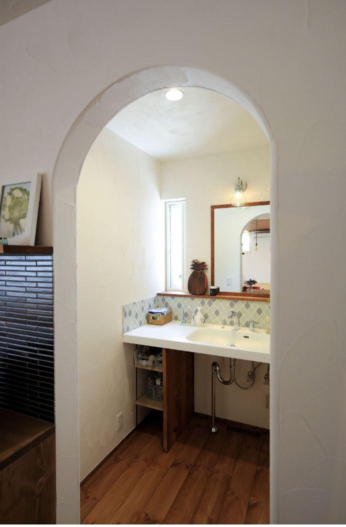 アイジースタイルハウス【自然素材、間取り、平屋】アーチの垂れ壁で緩やかに仕切られた洗面室。カウンターは車椅子でも楽に使えるよう、高さと奥行きに配慮した。やさしい色合いのタイルがアクセントに。脱衣室と離したことで、誰かが入浴中でも手洗いや歯磨きが可能に