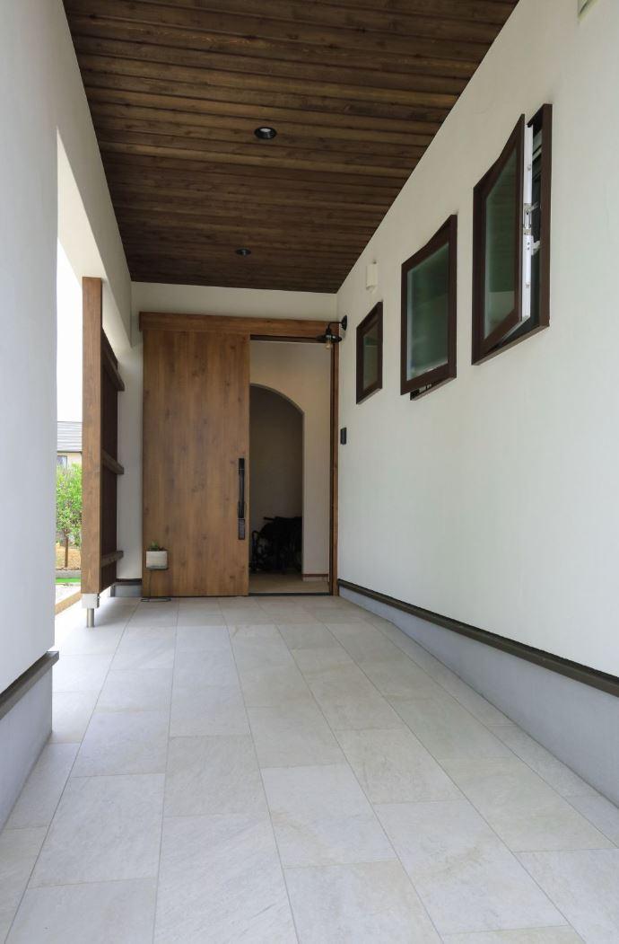 アイジースタイルハウス【自然素材、間取り、平屋】カーポートから緩やかなスロープを渡って、玄関へとつながるアプローチ。レッドシダーの軒天井が雨を凌いでくれる
