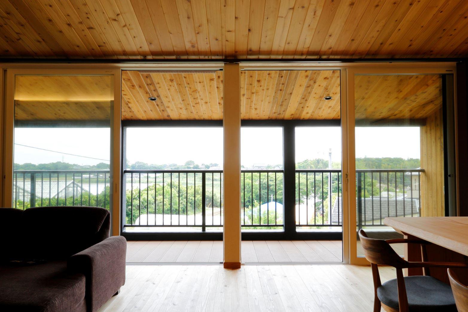 アイジースタイルハウス【子育て、自然素材、間取り】壁面いっぱいに設置した大開口の向こうに美しい眺望が開ける。室内と屋外の天井を同じレッドシダーで統一し、リビングとデッキの床をフラットにつなげたことで、より開放感が生まれた
