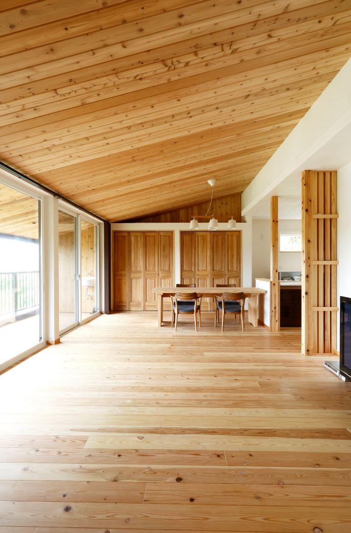 アイジースタイルハウス【子育て、自然素材、間取り】視界が奥まで伸びるLDKは開放感でいっぱい。キッチンとダイニングテーブルを横並びにしたことで家事効率も高まる。壁に漆喰を採用したことにより、焼肉やお好み焼きを食べても臭いが残らない。キッチン奥の扉は、実家と行き来するための第2の玄関