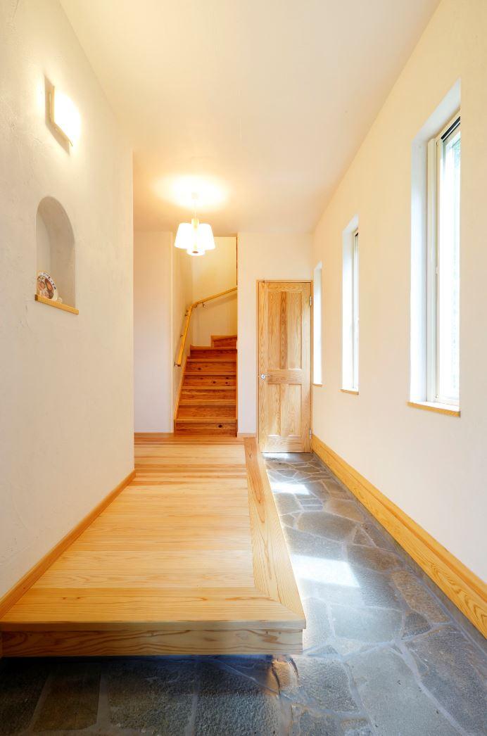 アイジースタイルハウス【子育て、自然素材、間取り】ゆったりとした土間玄関。子どもたちと横並びで靴を履けるようにしたいという奥さまの要望に応え、上がり框も大きめに。天然石の床が高級感を演出